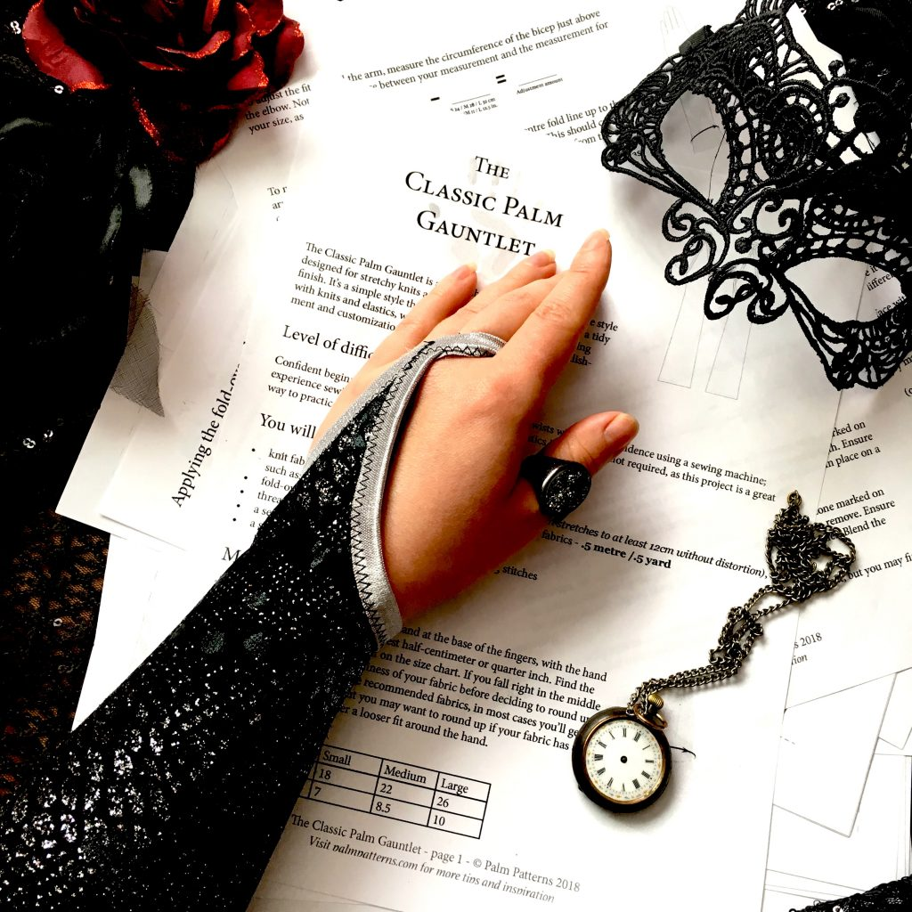 The Classic Palm gauntlet shown styled in black and silver, with a red rose, a black mask, and a pocket watch
